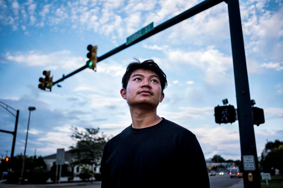 Hsa Win photo essay by Eli Hiller Hsa stands with his face upturned at a traffic intersection with clouds in the background