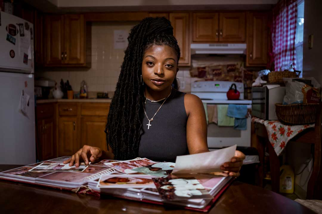 Photo Essay Kanyinsola Oye at the kitchen table with photographs strewn on top