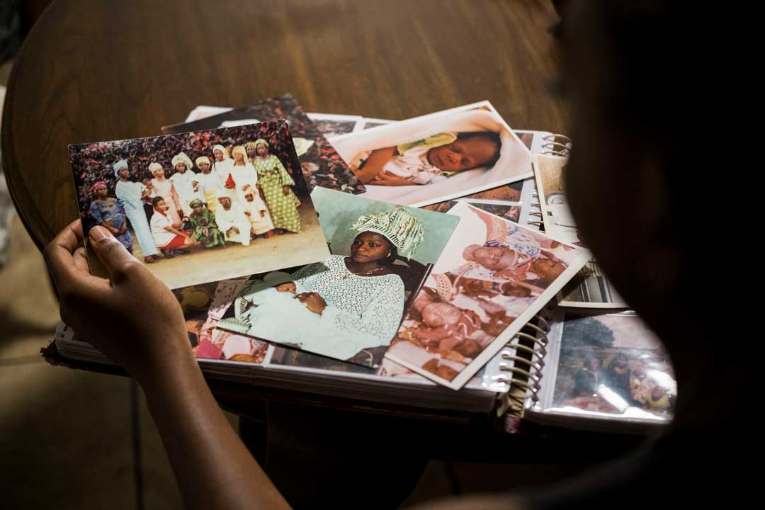 Photo Essay Kanyinsola Oye close up of family photographs strewn on top of the kitchen table